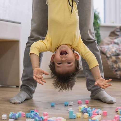 ילד צוחק בזמן שאבא שלו מחזיק אותו הפוך באוויר