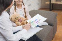 פסיכולוגית עם ילדה מסתכלת על ציור